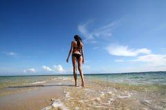 黑比基尼泳装的女孩走在白色海滩的 免版税库存图片