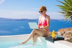 比基尼泳装的妇女与膝上型计算机一起使用在游泳池旁边 库存照片