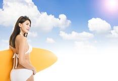比基尼泳装的妇女和举行surfboardÂ有云彩背景 库存图片