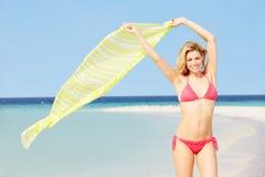 比基尼泳装的妇女在拿着布裙的美丽的热带海滩 库存照片