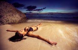 比基尼泳装的妇女在日落的海滩 免版税库存图片