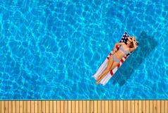 比基尼泳装的妇女在游泳池的可膨胀的床垫 免版税库存图片