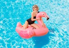 比基尼泳装的妇女在游泳池的可膨胀的床垫 免版税库存照片