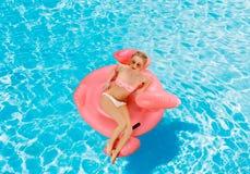 比基尼泳装的妇女在游泳池的可膨胀的床垫 库存图片