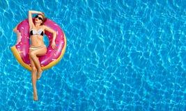 比基尼泳装的妇女在游泳池的可膨胀的床垫 免版税图库摄影