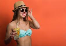 比基尼泳装的妇女有一份冷的饮料的 图库摄影