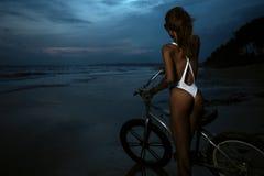 比基尼泳装的妇女有她的自行车的 免版税图库摄影