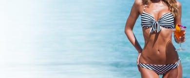 比基尼泳装的妇女有鸡尾酒的 免版税图库摄影