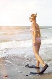 比基尼泳装的妇女有鸭脚板和风镜的在海滩 库存照片