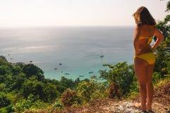 比基尼泳装的少妇在小山和看站立在与棕榈的seaahore海滩上 放松在水孑然  自然a 免版税库存照片