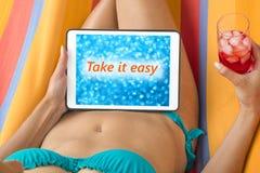 比基尼泳装的少妇在有片剂设备的一个吊床 库存照片