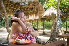 比基尼泳装的年轻美丽和愉快的亚裔韩国妇女吃午餐早午餐或早餐在热带天堂海滩胜地 免版税图库摄影