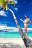 比基尼泳装的年轻美丽的女孩用在棕榈树的椰子 免版税库存照片