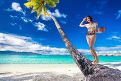 比基尼泳装的年轻美丽的女孩用在棕榈树的椰子 免版税库存图片