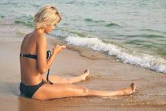 比基尼泳装的年轻美丽的被晒黑的妇女有在海滩的手机的 图库摄影