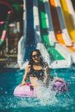 比基尼泳装的微笑的妇女在水池坐橡胶环 免版税库存图片