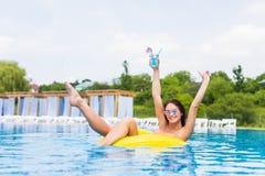 比基尼泳装的性感的妇女享用夏天太阳和晒黑在水池的假日期间的与鸡尾酒 顶视图 池游泳妇女 性感 免版税库存照片