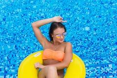 比基尼泳装的性感的妇女享用夏天太阳和晒黑在水池的假日期间的 顶视图 池游泳妇女 biki的性感的妇女 免版税库存照片