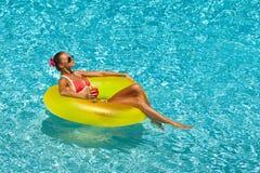 比基尼泳装的性感的妇女享用夏天太阳和晒黑在水池的假日期间的 免版税库存照片