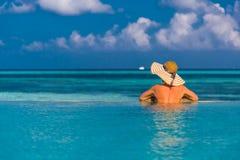 比基尼泳装的性感的妇女在水池,观看海背景在马尔代夫 图库摄影