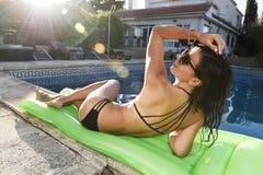 比基尼泳装的性感的妇女有有美好的身体的放松的晒黑airbed在日落的游泳池 免版税库存照片