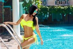 比基尼泳装的性感的美丽的女孩在水池在旅馆里 夏天v 库存图片
