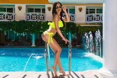 比基尼泳装的性感的美丽的女孩在水池在旅馆里 夏天v 免版税库存图片