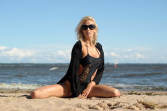 黑比基尼泳装的性感的金发碧眼的女人 免版税库存照片