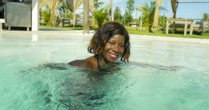 比基尼泳装的愉快和美丽的黑人非裔美国人的妇女获得乐趣在嬉戏热带海滩胜地的游泳场轻松和 免版税库存照片