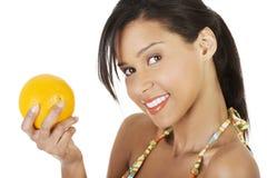 比基尼泳装的愉快的夏天妇女用桔子。 免版税库存图片