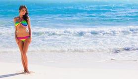 比基尼泳装的愉快的女孩在海边 图库摄影
