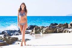 比基尼泳装的愉快的女孩在海边 免版税图库摄影