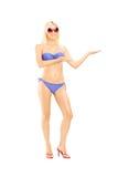 比基尼泳装的愉快的白肤金发的女性打手势用她的手的 免版税图库摄影