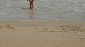 比基尼泳装的无忧无虑的妇女从有波浪的海出来喜欢晒日光浴和海滩假期 影视素材