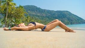 比基尼泳装的晒日光浴美丽,苗条的女孩 图库摄影