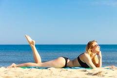 比基尼泳装的暑假女孩晒日光浴在海滩的 免版税库存图片