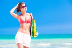 比基尼泳装的有海滩的妇女和太阳镜请求 免版税库存照片