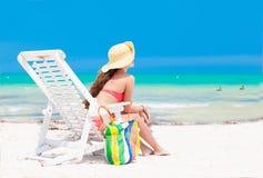 比基尼泳装的有海滩的少妇和草帽请求 库存照片