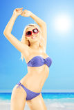 比基尼泳装的激动的女性享用在海滩的 库存图片