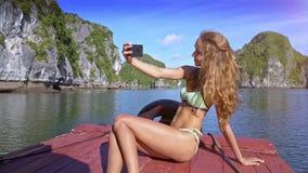 比基尼泳装的特写镜头俏丽的女孩在天蓝色的海湾的弓做Selfie 影视素材