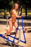 比基尼泳装的特写镜头白肤金发的女孩在步进训练在运动场 免版税库存照片