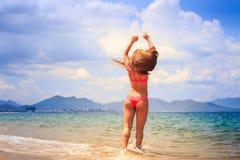 比基尼泳装的白肤金发的亭亭玉立的体操运动员站立在海边缘的后侧方  免版税库存图片