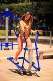 比基尼泳装的白肤金发的亭亭玉立的女孩在步进站立在运动场 免版税图库摄影