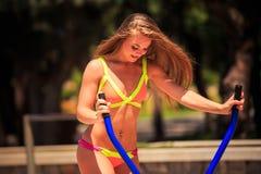 比基尼泳装的白肤金发的女孩在步进训练在运动场 库存照片