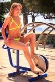 比基尼泳装的白肤金发的女孩坐室外自行车模拟器微笑 免版税库存照片