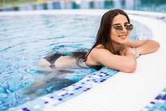 黑比基尼泳装的秀丽妇女和sunlasses在游泳池放松 时兴的纵向 比基尼泳装和太阳镜的端庄的妇女 免版税库存照片