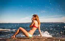 比基尼泳装的笑俏丽的女孩在海洋旁边,她由碰撞的波浪飞溅在岩石 免版税库存照片
