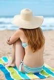 比基尼泳装的红头发人在海滩的妇女和Sunhat 库存照片
