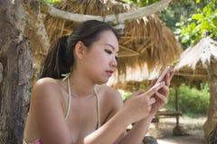比基尼泳装的美丽和愉快的亚裔韩国妇女使用手机的互联网在热带天堂海滩胜地在棕榈树下 库存图片