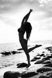 黑比基尼泳装的美丽的亭亭玉立的妇女 海滩、沙子和石头 免版税库存图片